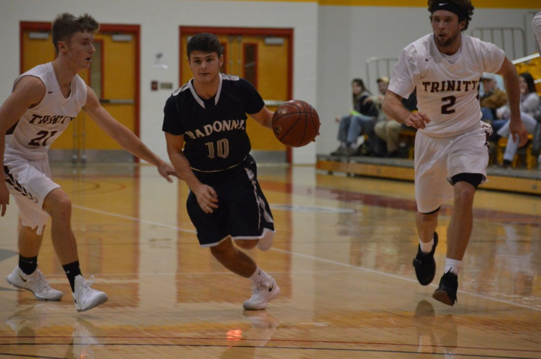 Photo by Kyle Lutz Madonna's Angelo Gurrera (10) runs the fast break as Trinity's Briston Bennett (21) gives chase Friday at Wheeling Jesuit.