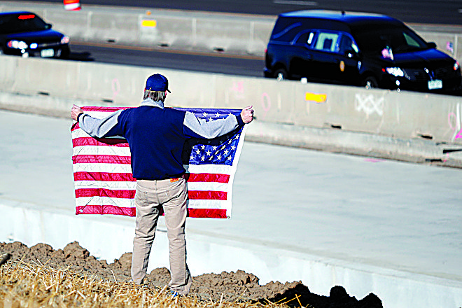David Morgan of Highlands Ranch Colo. holds an American flag as a procession of law enforcement vehicles accompany a hearse carrying the body of a sheriff's deputy shot and killed while responding to a domestic disturbance Sunday Dec. 31 2017