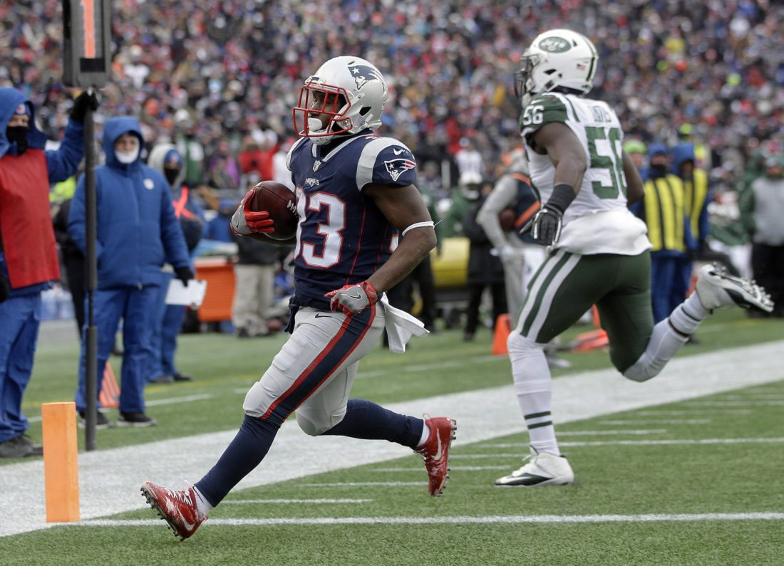 New England Patriots running back Dion Lewis (33) scores a touchdown in front of New York Jets linebacker Demario Davis (56) during the first half of an NFL football game, Sunday, Dec. 31, 2017, in Foxborough, Mass. (AP Photo/Steven Senne)