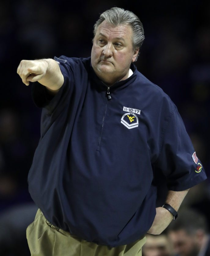 West Virginia head coach Bob Huggins directs his team during the first half of an NCAA college basketball game against Kansas State in Manhattan, Kan., Monday, Jan. 1, 2018. (AP Photo/Orlin Wagner)