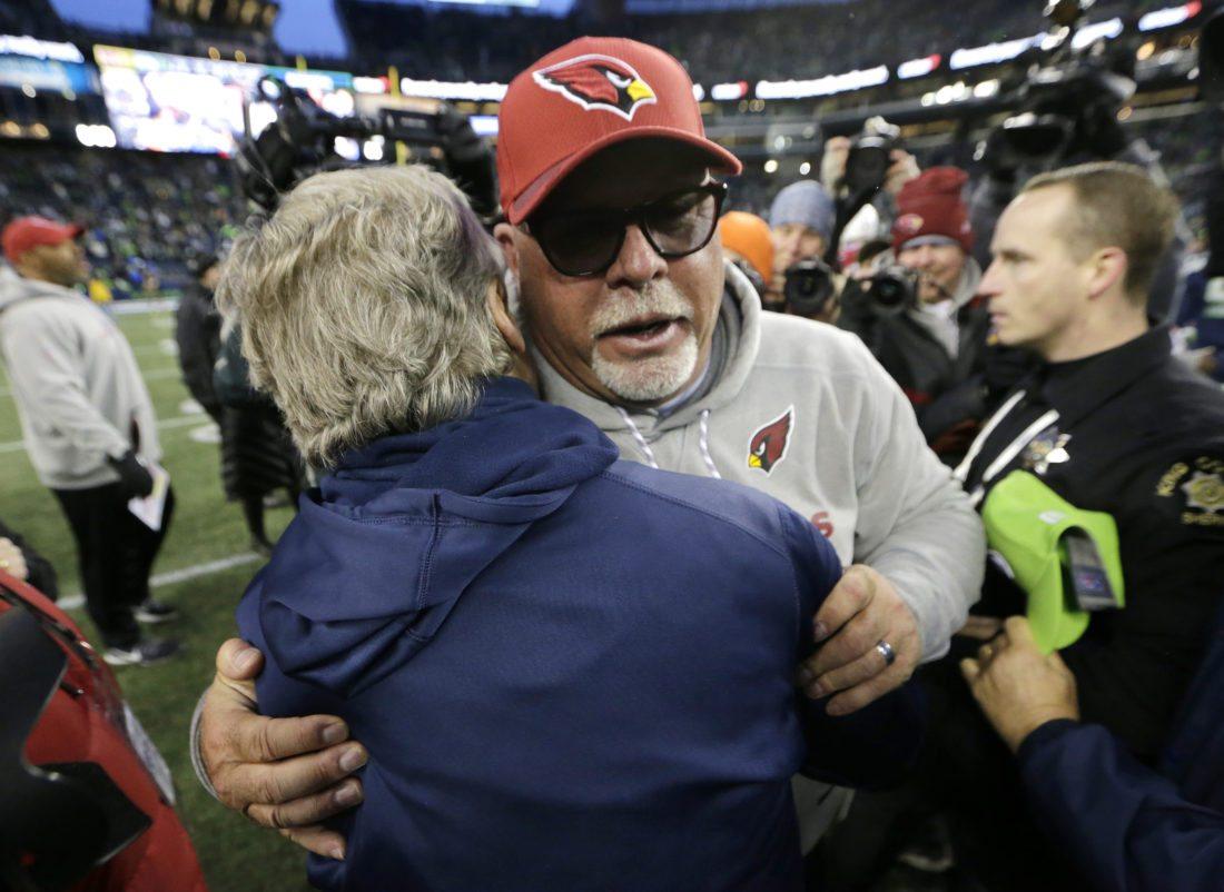 Arizona Cardinals head coach Bruce Arians, front right, hugs Seattle Seahawks head coach Pete Carroll, left, after an NFL football game, Sunday, Dec. 31, 2017, in Seattle. (AP Photo/John Froschauer)