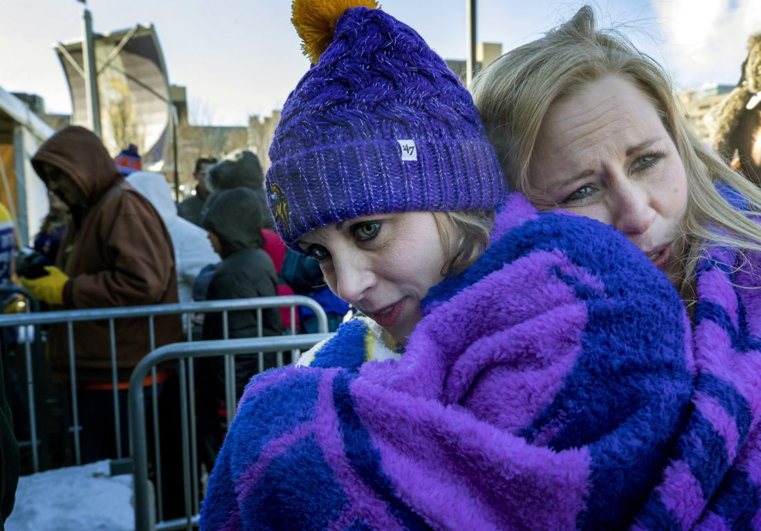 April Nickila and Christina Liesmaki try to stay warm while waiting in subzero temperatures to enter U.S. Bank Stadium to watch an NFL football game between the Chicago Bears and Minnesota Vikings, Sunday, Dec. 31, 2017, in Minneapolis. (Carlos Gonzalez/Star Tribune via AP)