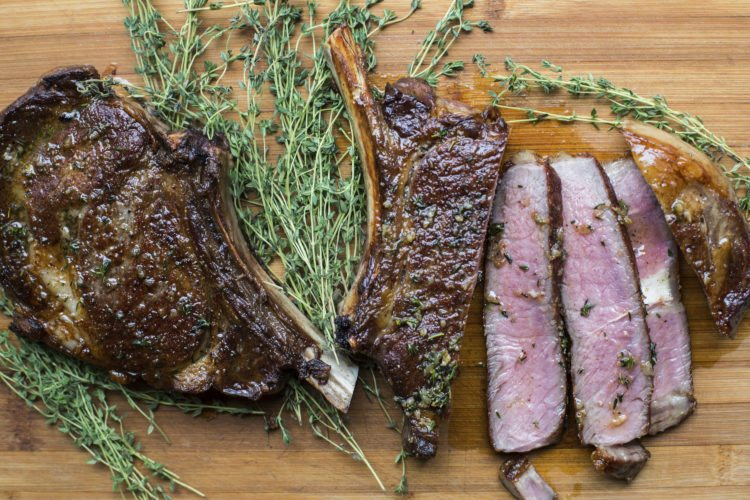 This September 2017 photo shows ribeye steaks with thyme-garlic butter in New York. This is a classy take on a restaurant-quality steak dinner, and it's only 30 minutes from start to finish. (Sarah Crowder via AP)