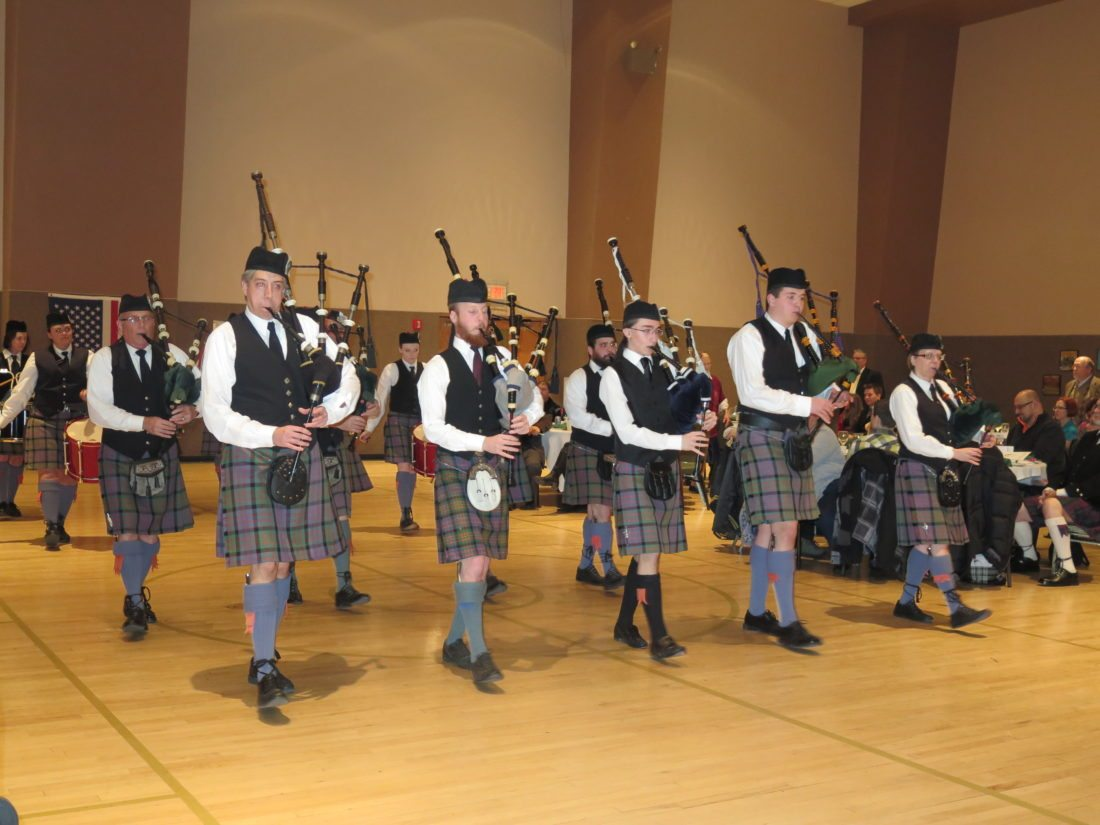 Photo Provided Franciscan University of Steubenville freshman Brendan Gormley, second from right, and Martins Ferry resident Betsy Bethel-McFarland, far right, march with the Macdonald Pipe Band of Pittsburgh during a past Robert Burns Supper.