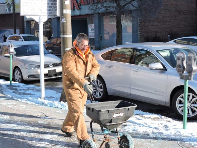 Ed Anderson, an employee with the Anthony Wayne Oil Corp., spreads salt on the             sidewalk in front of one of the company's            surface parking lots on Main Street in            downtown Wheeling. Photo by                     Casey Junkins