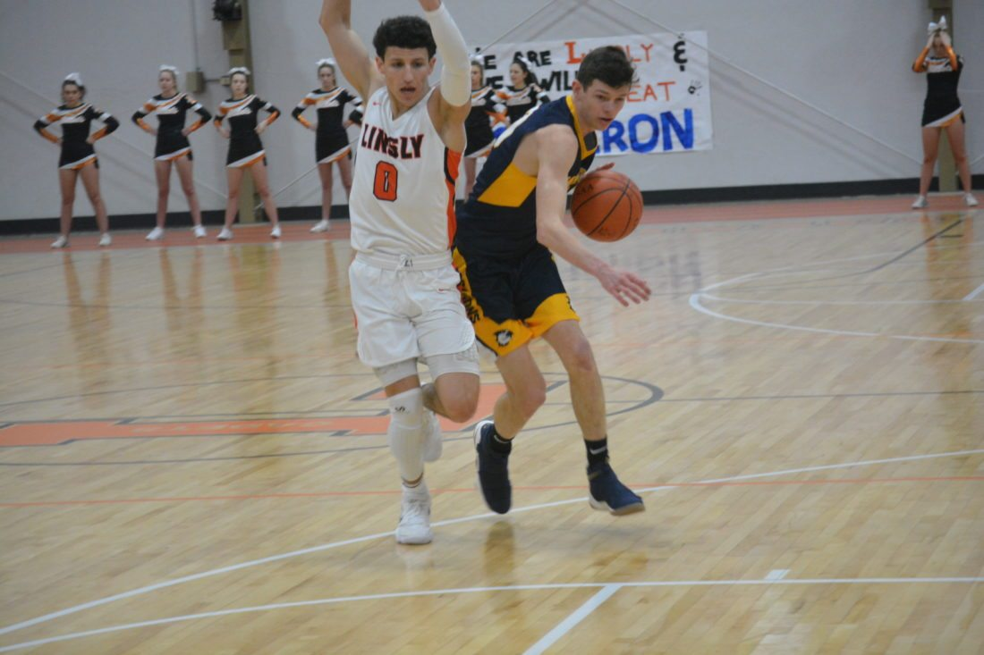 Photo by Josh Strope Cameron's Travis Mickey, right, brings the ball up the court against the defense of Linsly's Jimmy Zecca during their game Tuesday in Wheeling.