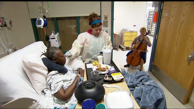 In this Oct. 11, 2017 image from video, cellist Martha Vance plays for a patient at Medstar Georgetown University Hospital in Washington DC. Musicians and dancers are part of the Georgetown Lombardi Comprehensive Cancer Center's arts and humanities program. (AP Photo/Tom Sampson)