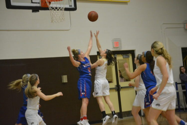 John Marshall's Shay Straughn, right, lifts up a shot as Wheeling Park's Brionna Gray (3) defends during the first quarter Wednesday in Moundsville.