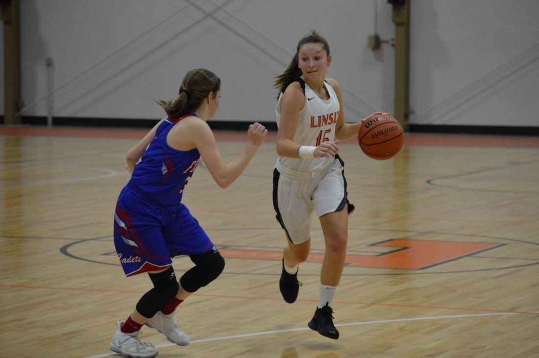 PHOTO BY JOSH STROPE Linsly's Josie Purpura (15) moves the ball up the court as Fort Frye freshman Lexi Huck defends during Thursday night's girls' basketball game at Stifel Field House in Wheeling.