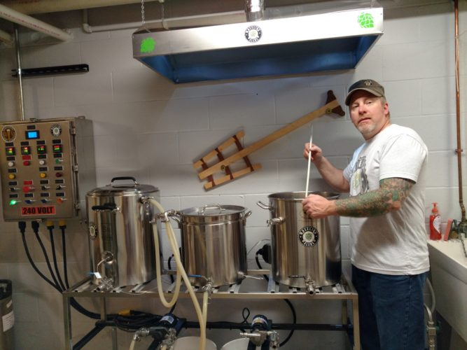 "Kurt ""Bug"" Reed of Colerain is shown stirring a bot of homebrew on the new electric system he built in his basement. The dedicated homebrewer grows his own hops and has a tattoo of hops on his arm."