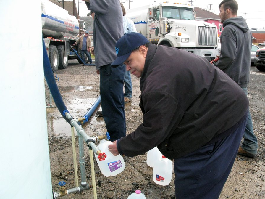 Eric Young of Steubenville fills a plastic jug with water at the Urban  Mission warehouse parking lot Friday.  Photo by Mark Law