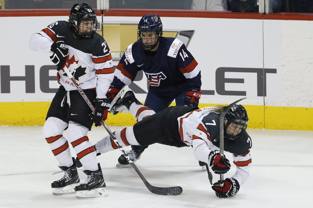 FILE - In this Dec. 5, 2017, file photo, Canada's Laura Stacey (7) falls after a collision with Canada's Emily Clark (26) and United States' Brianna Decker (14) during the first period of a hockey game in Winnipeg, Manitoba. Stacey usually wears a necklace with the No. 7 around her neck that matches the sweater she wears for Team Canada. In her family, it's much more a tradition than just a number. That's the No. 7 Hockey Hall of Fame defenseman King Clancy wore playing for the Ottawa Senators and Toronto Maple Leafs. And the late Clancy, the man who has an annual NHL award named in his honor, is not just an old hockey name to Stacey. He's her great-grandfather and why Stacey is hoping to add a new chapter to the family's hockey history chasing Olympic gold for Canada. (John Woods/The Canadian Press via AP, File)
