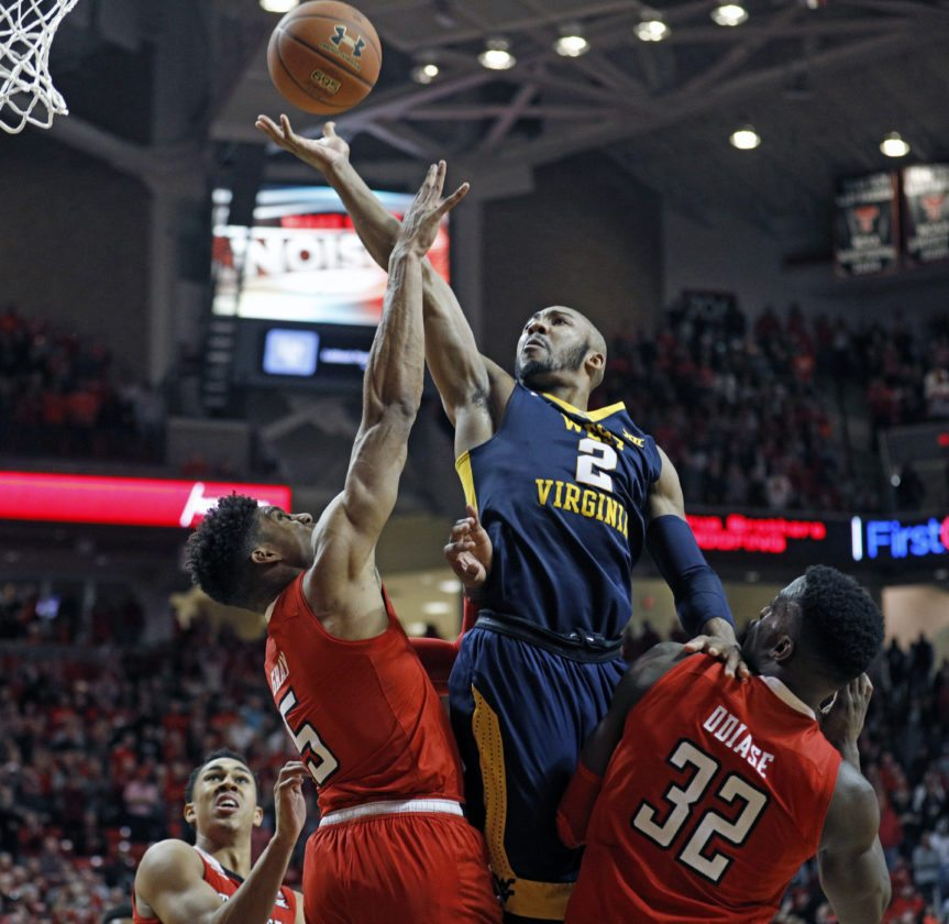 West Virginia's Jevon Carter (2) lays up the ball over Texas Tech's Justin Gray (5) and Norense Odiase (32) during the second half of an NCAA college basketball game Saturday, Jan. 13, 2018, in Lubbock, Texas. (AP Photo/Brad Tollefson)