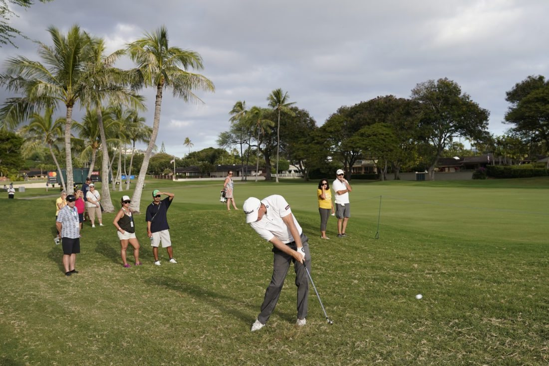 Tom Hoge, center, hits his ball out of the rough back into play on the 16th fairway during the third round of the Sony Open golf tournament, Saturday Jan. 13, 2018, in Honolulu. (AP Photo/Marco Garcia)