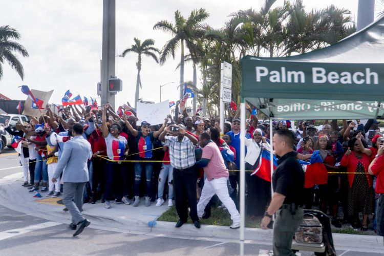Anti-Trump protesters line the sidewalks as President Donald Trump's motorcade returns to Mar-a-Lago in West Palm Beach, Fla., Monday, Jan. 15, 2018, after Trump played golf at Trump International Golf Club. (AP Photo/Andrew Harnik)