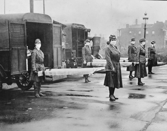 In this October 1918 photo made available by the Library of Congress, St. Louis Red Cross Motor Corps personnel wear masks as they hold stretchers next to ambulances in preparation for victims of the influenza epidemic. A century after one of history's most catastrophic disease outbreaks, scientists are rethinking how to guard against another super-flu like the 1918 influenza that slaughtered tens of millions as it swept the globe in mere months.   (Library of Congress via AP)