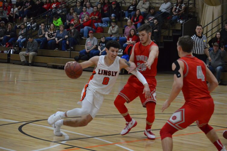 Photo by Cody Tomer Linsly's Jimmy Zecca (0) goes to the basket against the defense of River's Tanner Brown.