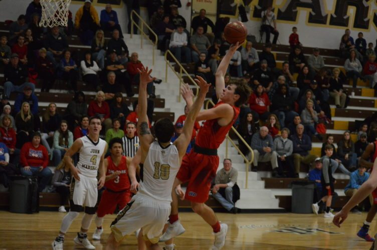 Photo by Cody Tomer Wheeling Park's Alex Dunlevy goes up for a shot as John Marshall's Bryce Yoho (2) defends. The Monarchs' Adam Miller (4) and the Patriots' DeVaughn McWhorter (3)look on during Friday night's game.