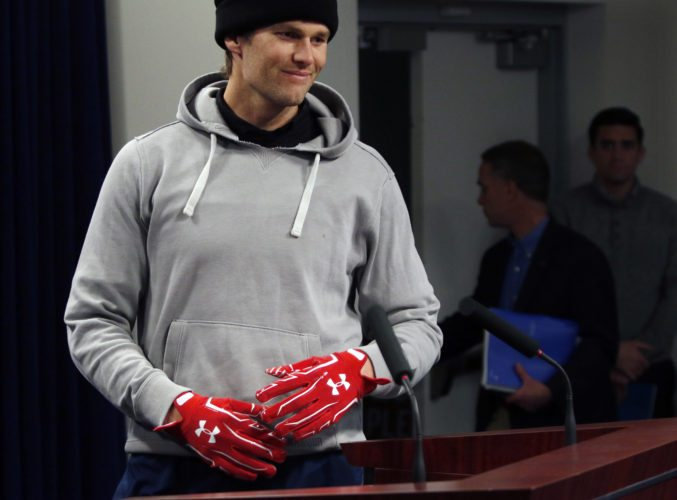 New England Patriots quarterback Tom Brady wears gloves as he arrives to speak to the media, Friday, Jan. 19, 2018, in Foxborough, Mass. The Patriots host the Jacksonville Jaguars in the AFC championship on Sunday in Foxborough.(AP Photo/Bill Sikes)