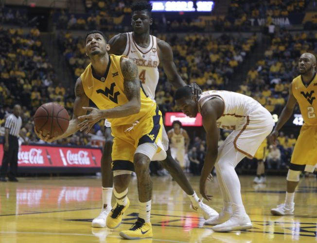 West Virginia guard James Bolden (3) shoots the ball after stealing it from Texas guard Kerwin Roach II (12) during the second half of an NCAA college basketball game Saturday, Jan. 20, 2018, in Morgantown, W.Va. West Virginia defeated Texas 86-51. (AP Photo/Raymond Thompson)