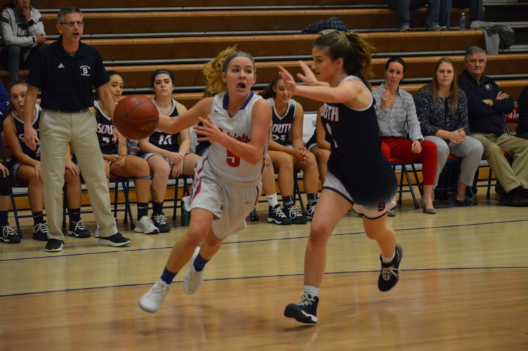 Photo by Josh Strope Wheeling Park's Kylie McKennen (5) drives to the basket as Parkersburg South's Kenzie Johnson defends Saturday night at The Palace on the Hill.