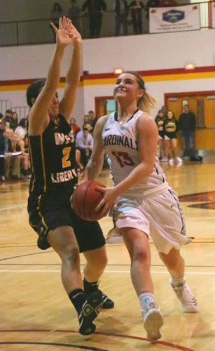 Photo by Joe Lovell Wheeling Jesuit's Monica Burns (13) goes in for a layup while West Liberty's McKenna Shives defends.