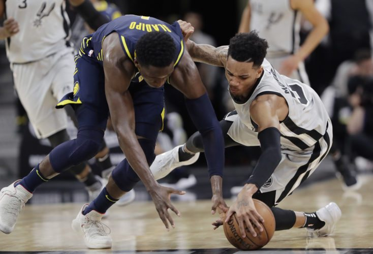 Indiana Pacers guard Victor Oladipo, left, and San Antonio Spurs guard Dejounte Murray, right, battle for the ball during the second half of an NBA basketball game, Sunday, Jan. 21, 2018, in San Antonio. (AP Photo/Eric Gay)
