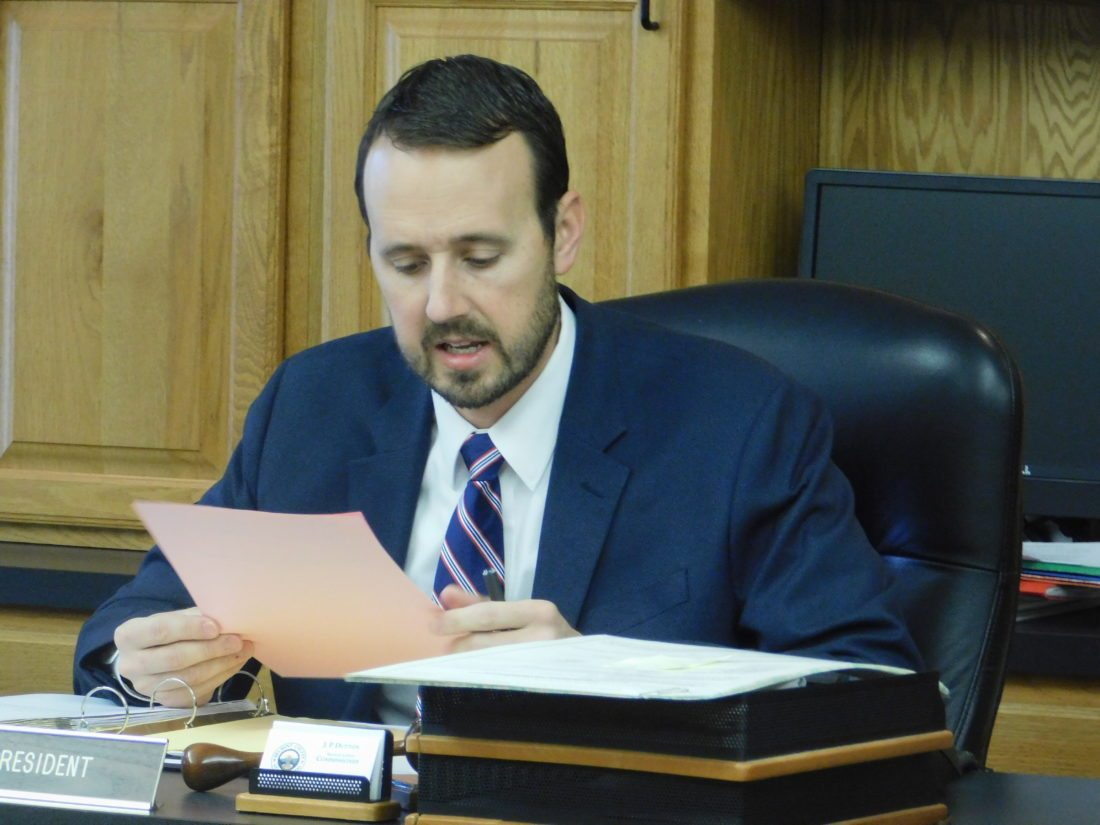 Photo by Robert A. DeFrank Belmont County Commissioner J.P. Dutton speaks as he reviews a document during a Wednesday meeting during which commissioners voted to terminate an agreement with Washington County's building department.