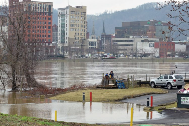 Photos by Scott McCloskey Wheeling Island residents keep an eye on the level of the Ohio River on Friday. Several people are pictured looking over the river from the shore behind on South Front Street.