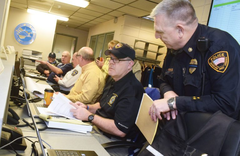 Photo by Scott McCloskey As local officials meet at the Ohio County Emergency Management Agency command center in the basement of the City-County Building in Wheeling Friday, Wheeling Police Chief Shawn Schwertfeger, second from right, and Wheeling Deputy Police Chief Martin Kimball, far right, talk prior to the start of the meeting.