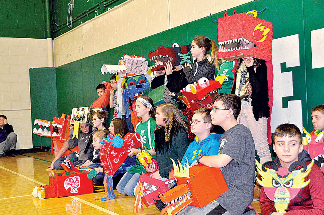 A group of Elkins Middle School sixth-graders show off masks they made for Tuesday's dragon parade. The annual event is designed to teach students about Chinese culture and to celebrate the Chinese New Year.