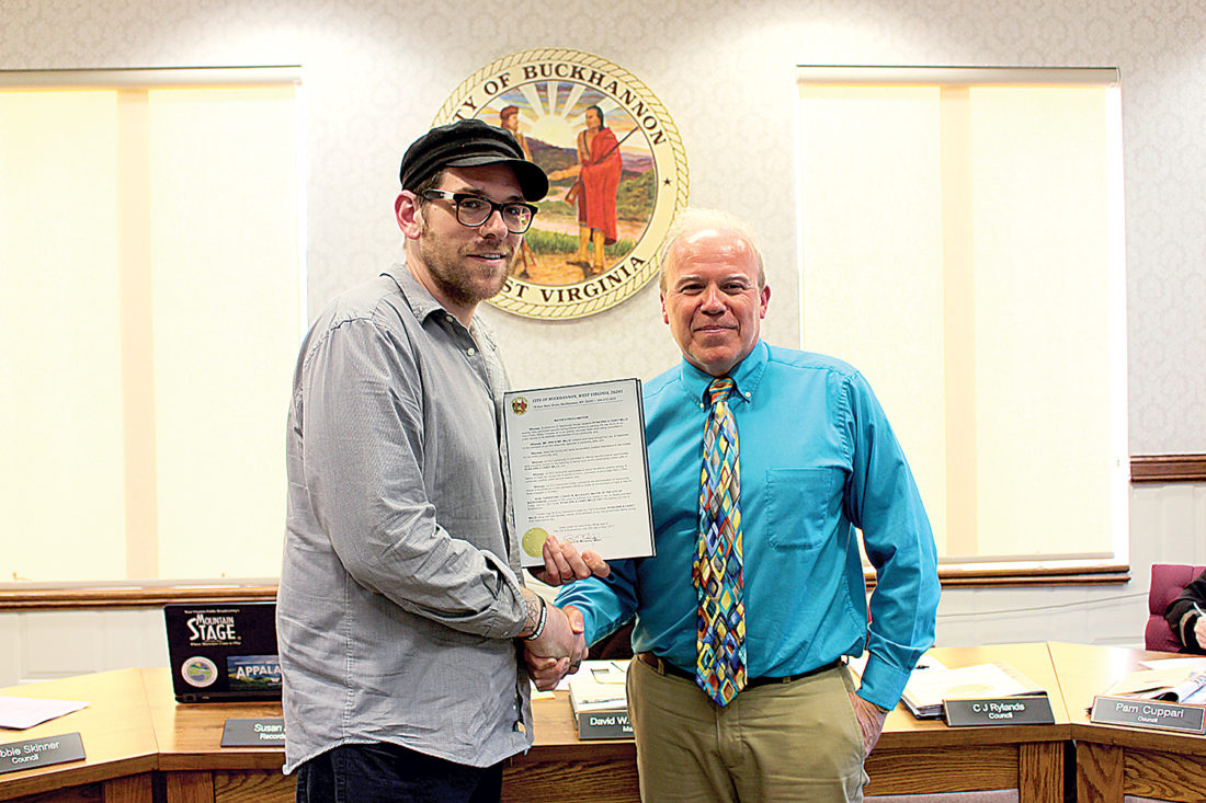 Ryan Zirk, left, and Casey Mills, not pictured, are recognized Thursday by Buckhannon Mayor David McCauley, right, for the artwork the pair completed on the bay doors of the Buckhannon Fire Department. The two will be honored on April 27.