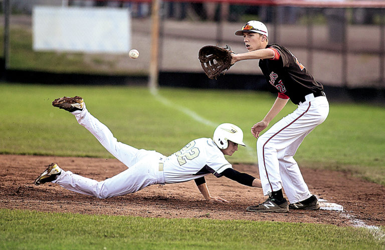 The Inter-Mountain photo by Kevin Hostetler Elkins first baseman David Gainer reaches for the ball as Lincoln's Dustin Marks slides in safely during the Tigers' 12-8 Class AA Region 2, Section 1 semifinal win on Saturday. Elkins will face Bridgeport at 6 p.m. today for the sectional title.
