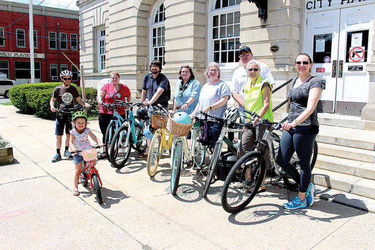 Several people who participated in National Bike to Work Day took a pit stop at Elkins City Hall to visit with Mayor Van Broughton on Friday. Pictured, in front, is Hallie Riddle; second row from left, Joey Riddle, Donna Smith, Shane Yeager, Emily Prentice, Kathryn Prentice, Karen Carper and Nicki Hinkle; and in back, Broughton.