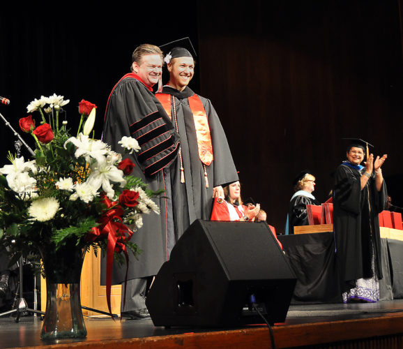 The Inter-Mountain photo by Beth Henry-Vance Davis & Elkins College President Chris A. Wood, left, presents a Bachelor of Arts degree Saturday to Will Roboski, of Elkins, after the graduate danced across the stage to receive his diploma.