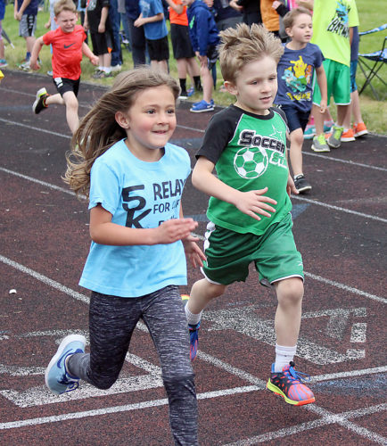 The Inter-Mountain photo by Brooke Binns Macie Sturdivant, left, and Jade Joss, right, race across the finish line in the 100-meter fun run on Tuesday at the Mayor's Intra-City Johnny Keller Track Meet in Elkins.