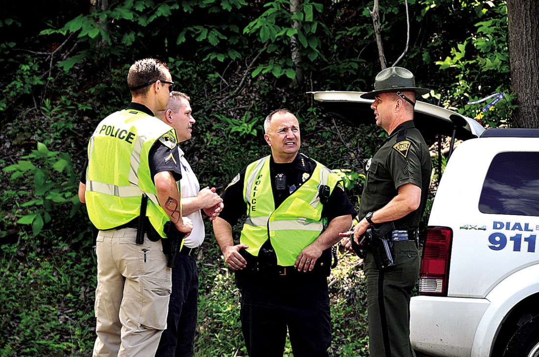 The Inter-Mountain photos by Tim MacVean Law enforcement officials with the Barbour County Sheriff's Department, West Virginia State Police and Philippi Police Department converse after an explosion at Midland Resource Recovery, a gas company located along Barbour County Highway in Moatsville, which took the lives of two people and forced another to be taken by helicopter to a hospital in Morgantown Wednesday afternoon.