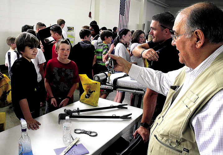 The Inter-Mountain photo by Beth Henry-Vance Interim Elkins Police Chief J.C. Raffety, from right, and Patrolman Christopher Boatwright speak to Elkins Middle School students about law enforcement jobs and even demonstrate proper handcuff usage during Wednesday's career fair at the Phil Gainer Community Center.