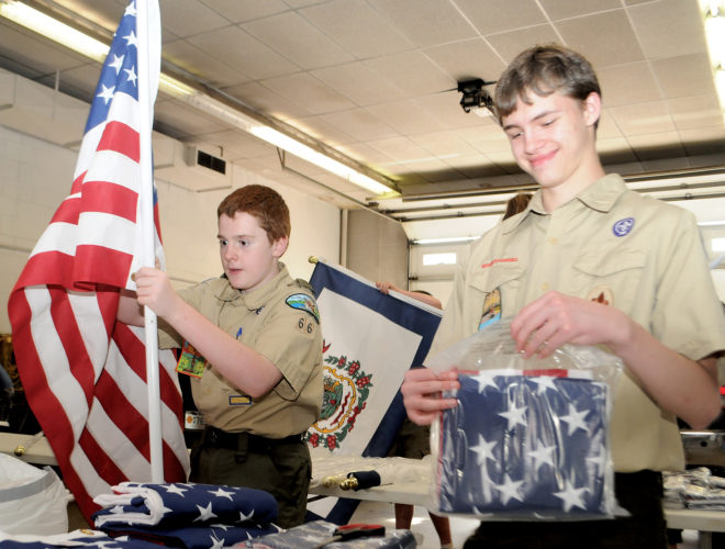 The Inter-Mountain photo by Beth Henry-Vance Garrett Swecker, left, William Marks, right, and other members and leaders with Boy Scouts of America Troop 66 of Beverly gather Tuesday evening at the Elkins Fire Department to assemble flags that will decorate streets throughout Elkins.