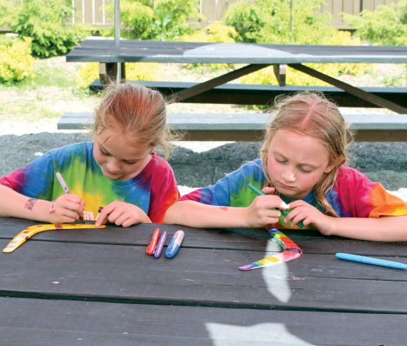 The Inter-Mountain photo by Brooke Binns The Elkins-Randolph County YMCA summer camp kicked off this week. During their first week, campers are enjoying activities related to the theme 'Around the World.' Gabrielle Dempsey, left, and Lilian Burda, right, enjoy a sunny day decorating boomerangs in the green space outside of the Y.