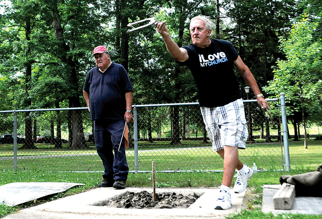 The Inter-Mountain photos by Beth Henry-Vance Donnie Coberly, right, of Glenmore, pitches horseshoes recently at Elkins City Park with Burton Hare Sr., of Gilman. The Elkins Horseshoe Club welcomes new members, and it meets twice a week during the summer and into late September.
