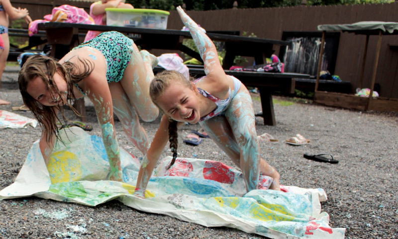 The Inter-Mountain photo by Brooke Binns Despite a forecast calling for rain on Friday, campers at the Elkins Randolph County YMCA enjoy the warm temperatures outside. Lexus Caynor, 11, left, and Lilly Betler, 9, slip and slide during a challenging round of shaving cream Twister.
