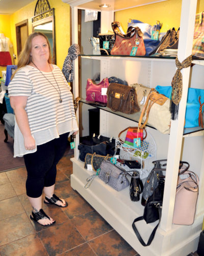 The Inter-Mountain photo by Lydia Rhodes The Wooden Hanger's new owner, Heather Harris, displays purses and handbags offered in her store. Purse brands include Dooney and Bourke, Coach, Kate Spade, Vera Bradley, Michael Kors, Spartina 449 and more.