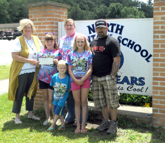 The Inter-Mountain photo by Beth Henry-Vance Cynthia Bodkin, left, principal at North Elementary School in Elkins, presents a check Monday to incoming fifth-grader Madison Taylor and her family, parents Paula and Jonathan Taylor, older sister Morgan and younger brother Miner. The family lost all their possessions in a house fire, and they are thankful for the community support.