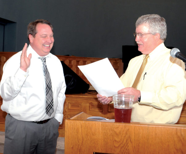 The Inter-Mountain photo by Beth Henry-Vance Carl Nichols, left, the incoming president of the Elkins Rotary Club, takes his oath of office with the help of Mike Ellis, immediate past president, during Monday night's Rotary Installation Dinner, which took place at The Arts Center in Elkins.