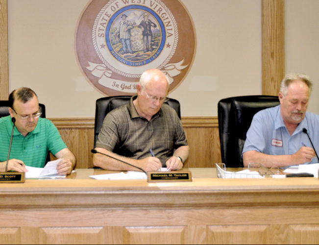 The Inter-Mountain photo by Tim MacVean From left, Randolph County Commissioner Mark Scott, Commission President Mike Taylor and Commissioner Chris See pay bills for the end of fiscal year 2016/2017 – which runs from July 1 through Friday – during a special meeting Tuesday morning. The next regular Commission meeting is scheduled for 1:30 p.m. on July 5.