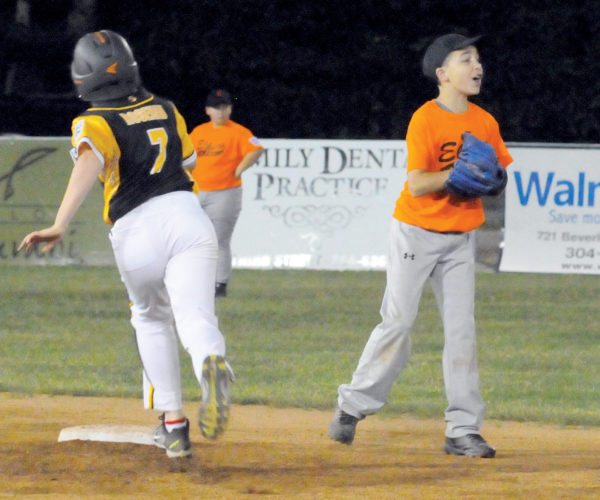 The Inter-Mountain photos by Brad Johnson An Elkins infielder shouts for the ball as a Tucker County player rounds second base Tuesday during 10-11-year-old District 8 tournament play at Riverbend Park in Elkins. Tucker County won the tournament championship game, defeating Elkins 11-1. Also on Tuesday at Riverbend, Summersville won the 11-12 District 8 Tournament, with Tygart Valley as the runner-up squad.