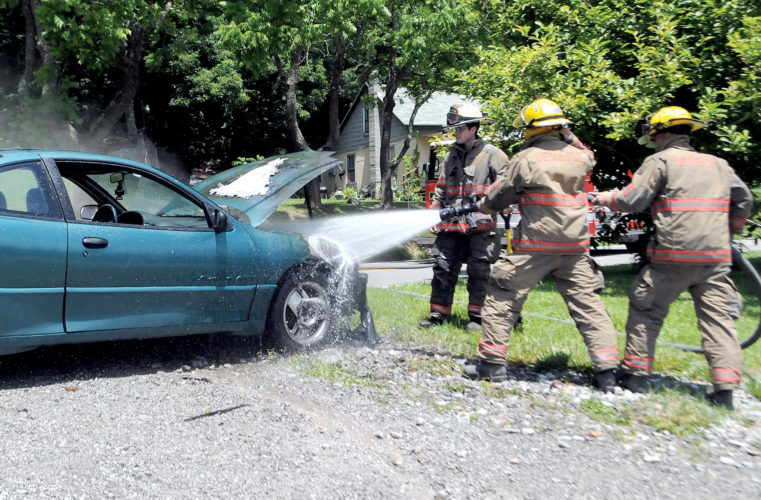 The Inter-Mountain photo by Beth Henry-Vance Lt. Robbie Moyer, left, and members of the Beverly Volunteer Fire Department respond Wednesday to a car fire along Files Creek Road. No injuries were reported, and Moyer said he just happened to be in the right place at the right time. The fire truck was traveling to the Randolph County 4-H Camp for a children's water activity when he spotted the car on fire. 'It was good that we were going by,' Moyer said. 'It could have been worse.'