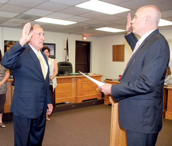 The Inter-Mountain photo by Beth Henry-Vance Gabriel J. 'Gabe' Devono takes the oath of office as the new superintendent of schools for Randolph County at the beginning of Tuesday's regular Board of Education meeting, led by Circuit Court Judge David H. Wilmoth, right.