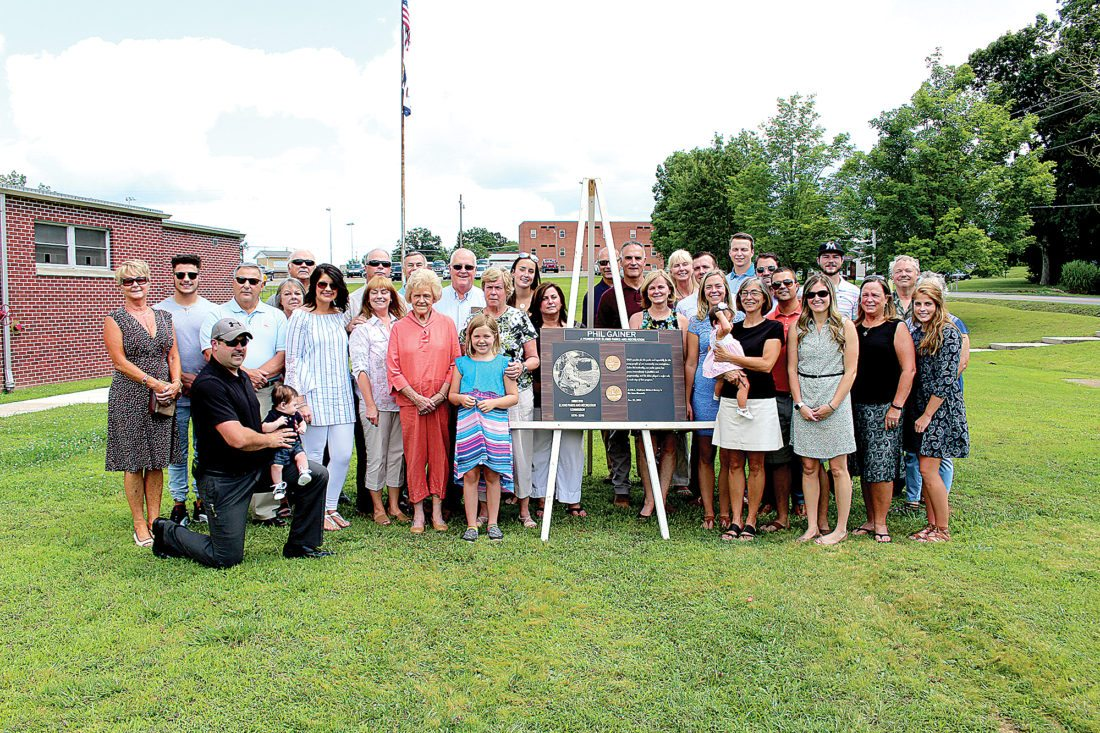 The Inter-Mountain photo by Brooke Binns Phil Gainer's family poses with a plaque that will be hung in Gainer's honor at the community center in Elkins.